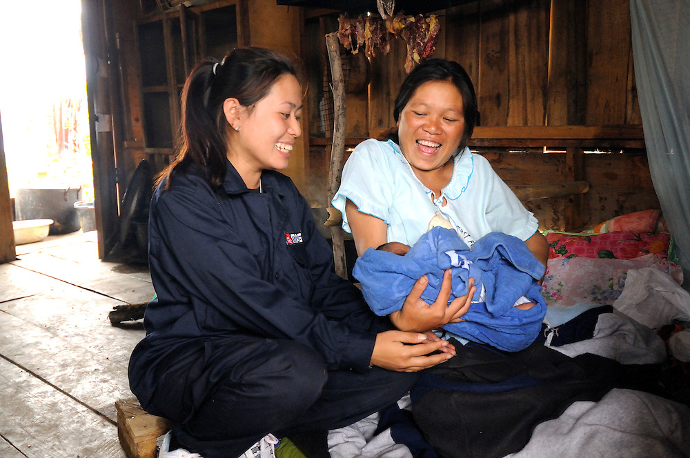 """Sia Thorthongyer, age 20, visits her supervisor, Mines Advisory Group (MAG) women's Team Leader, Peng Souvanthon, age 26, with her 2 day old son and 6 year old daughter at home.  Even at 8 months pregnant she worked in remote Nong Het field locations clearing bombs up until the day she gave birth. ..She says, """"I'm happy to have helped my village and made it more safe for farming.""""  And when asked about competing with the MAG men's demining teams she says """"Yes, if the men clear 2,000 sq m of land per day, then we women want to do even more.""""..Laos was part of a """"Secret War"""", waged within its borders primarily by the USA and North Vietnam.  Many left over weapons supplied by China and Russia continue to kill.  However, between 90 and 270,000 million fist size cluster bombs were dropped on Laos by the USA, with a failure rate up to 30%.  Millions of live cluster bombs still contaminate large areas of Laos causing death and injury.  The US Military dropped approximately 2 million tons of bombs on Laos making it, per capita, the most heavily bombed country in the world.  ..The women of Mines Advisory Group (MAG) work everyday under dangerous conditions removing unexploded ordinance (UXO) from fields and villages. ..***All photographs of MAG's work must include (either on the photo or right next to it) the credit as follows:  Mine clearance by MAG (Reg. charity)***."""
