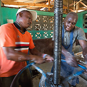 CAPTION: Operating the press to squeeze all the moisture out of the cassava. The team explains that the cassava they make stands out, boasting a reputation for superior quality. One of the main reasons for this is that they don't take the starch out of the plant when they grind it. Any that is pressed out during the moisture removal process is returned later. This ensures that nutrients are retained and saves OGKPS from having to add sugar to achieve a good taste, which their competitors do. ORGANIZATION: Organizasyon Gwoupman Kominotè Pawas Sakretè (OGKPS). LOCATION: #88 Laviolette (Monte Pa Desann), Cap-Haïtien, Haiti. INDIVIDUAL(S) PHOTOGRAPHED: Jean-Pierre Regel (left) and Elino Selondieu (right).