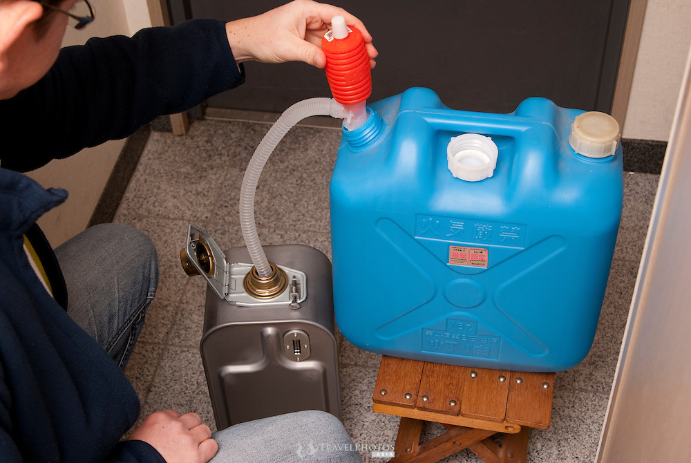 A man refilling his heaters kerosene can from a domestic jerry can.