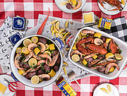 A styled photo of a Seafood boil with crab, lobster, shrimp, corn, and potatoes. Photo by Brandon Alms Photography
