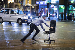 © Licensed to London News Pictures . 21/12/2013 . Manchester , UK . A man runs with an office chair across the road in front of a taxi . Christmas revellers out in the rain in Manchester on Mad Friday , the last Friday night before Christmas which is typically one of the busiest nights of the year for police and ambulance crews . Photo credit : Joel Goodman/LNP