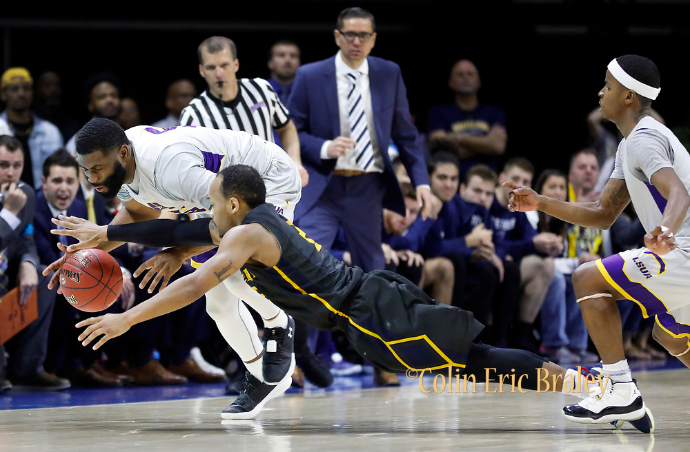 LSU Alexandria forward Trent Brinkley, left, and Graceland guard LT Davis, center, battle for a loose ball during the second half of a NAIA championship men's college basketball game, Tuesday, March 20, 2018, in Kansas City, Mo. Looking on is Graceland head coach, Craig Doty, top, and LSU guard Shannon James Jr. right.(AP Photo/Colin E. Braley)