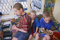 Three boys with autism sitting together in front room,