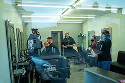 © Licensed to London News Pictures . 11/09/2020. Bolton , UK . Environmental Health Officers CAROLINE GREENEN and LEANNE RICHARDSON issue a direction order to close Scott's Barber Shop in Horwich for a minimum of seven days  , with immediate effect , pending a review of the business after ongoing reports of breaches at the business , including failure to observe social distancing, wear appropriate face coverings and reusing gowns between different customers . Police officers from Greater Manchester Police and Environmental Health Officers from Bolton Council respond to concerns of breaches of Coronavirus regulations , as stricter lockdown measures and a curfew on hospitality businesses are imposed in the borough to limit the spread of Covid-19 . Photo credit : Joel Goodman/LNP