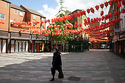 Woman wearing a face mask walks under red lanterns through Chinatown, which is eerily quiet and silent on empty streets as lockdown continues and people observe the stay at home message in the capital on 11th May 2020 in London, England, United Kingdom. Coronavirus or Covid-19 is a new respiratory illness that has not previously been seen in humans. While much or Europe has been placed into lockdown, the UK government has now announced a slight relaxation of the stringent rules as part of their long term strategy, and in particular social distancing.