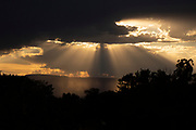 Sunset in Moab, Utah with trees in silhouette in the foreground and shafts of sunlight breaking through the cloud cover