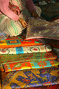 Indian woman selling pillows on a street in New Delhi with a shaft of sunlight hitting her
