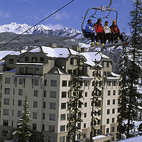 SKIING, Big Sky, Montana.  Ram Charger high speed quad lift rises in front of slopeside Summit Lodge.