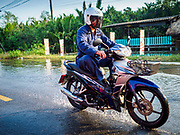 """22 JANUARY 2019 - SAMUT PRAKAN, THAILAND: Traffic on a flooded road that runs along the Chao Phraya River in Samut Prakan, south of Bangkok. The road was flooded by the high tide that occurred during a """"Super Moon"""" full moon made worse by rising sea levels and climate change.    PHOTO BY JACK KURTZ"""