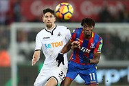 Wilfried Zaha of Crystal Palace ® & Federico Fernandez of Swansea city in action.Premier league match, Swansea city v Crystal Palace at the Liberty Stadium in Swansea, South Wales on Saturday 23rd December 2017.<br /> pic by  Andrew Orchard, Andrew Orchard sports photography.