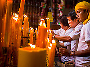 27 SEPTEMBER 2014 - BANGKOK, THAILAND:  People light prayer candles during the celebration of the Vegetarian Festival at the Chow Su Kong Shrine in Talat Noi, a Chinese enclave in Bangkok. The Vegetarian Festival is celebrated throughout Thailand. It is the Thai version of the The Nine Emperor Gods Festival, a nine-day Taoist celebration beginning on the eve of 9th lunar month of the Chinese calendar. During a period of nine days, those who are participating in the festival dress all in white and abstain from eating meat, poultry, seafood, and dairy products. Vendors and proprietors of restaurants indicate that vegetarian food is for sale by putting a yellow flag out with Thai characters for meatless written on it in red.   PHOTO BY JACK KURTZ