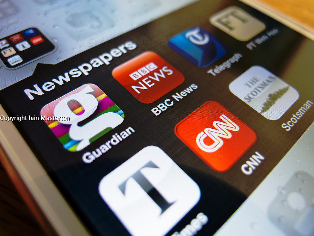 Detail of iPhone 5 smartphone screen showing newspaper app icons