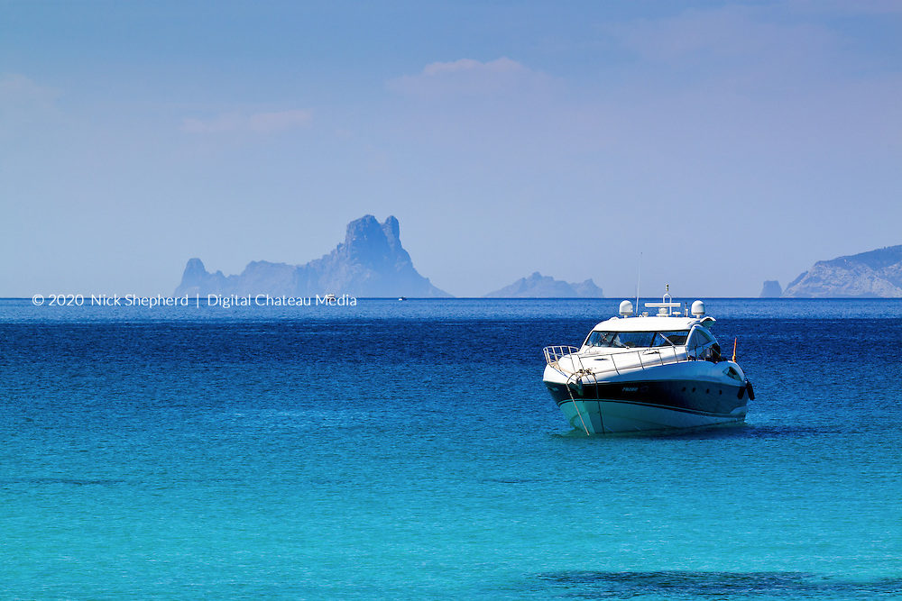 Es Vedra Island, Ibiza (Spain) seen from Formentera in the Mediterranean Sea. A motor yacht can be seen in the foreground, moored off the beach in the Balearic sunshine.