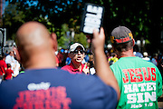 Robets Castro, of Fairfax VA, clashes with members of  the Los Angeles chapter of Bible Believers as they leave following a short parade where Pope Francis was driven on the streets around the Ellipse, south of the White House in Washington, District of Columbia, U.S., on Wednesday, Sept. 23, 2015.