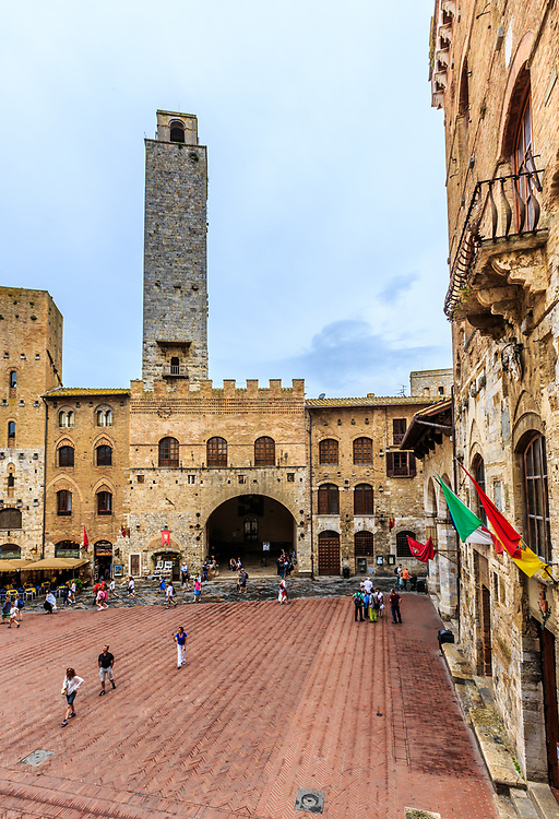 The Piazza del Duomo  in San Gimignano in Tuscany, Italy. The Piazza del Duomo has an intricate layout that took form in the late 13th century.  Important private and public buildings on the square include the Palazzo Comunale and the Palazzo Podesta, the mayor's house. Its vast arched loggia distinguishes the Palazzo Podesta.