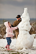 CHARLESTON, SC - February 13: A young girl puts the finishing touches on a snowman February 13, 2010 during a rare snow storm in Mt Pleasant, SC. About 3-inches of snow fell on the Charleston area, the first significant snow in 20-years.    (Photo Richard Ellis)