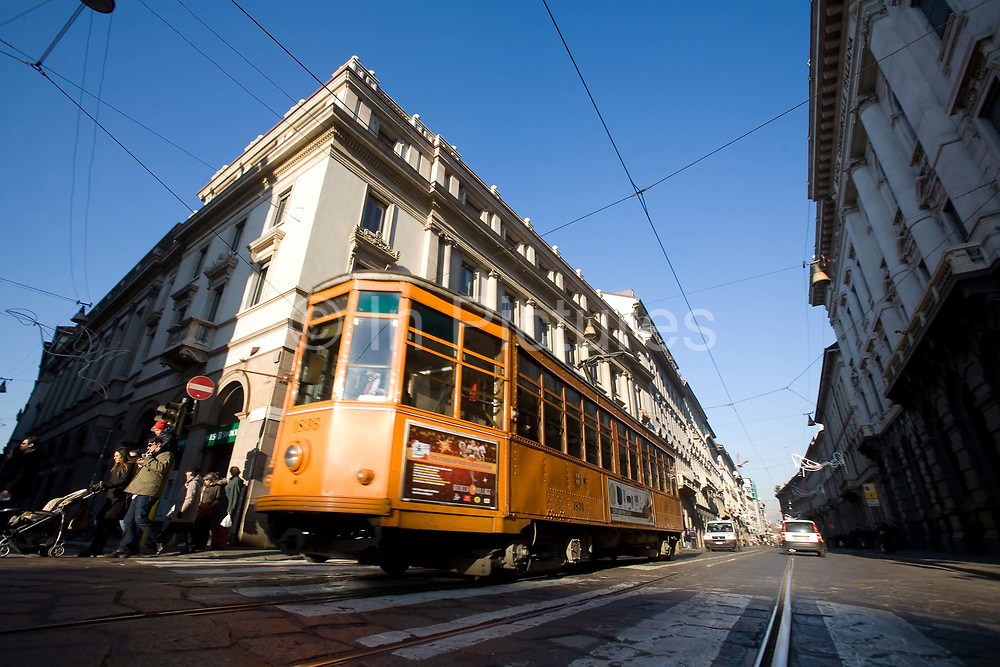 An old tram rumbles along a cobbled street in central Milan on 8th December 2008 in Milan, Italy. After many years of closures and decline, the tram network has undergone restoration and expansion since 1994.