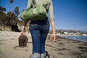 A woman, carrying her sandals, takes a stroll down Laguna Beach, California.