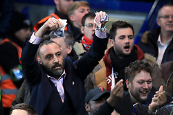 An Arsenal fan waves bank notes at the Chelsea fans during the Carabao Cup Semi Final, First Leg match at Stamford Bridge, London.