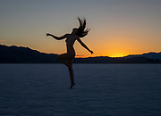 Nude woman flipping her head back and hair flying at sunset on the Bonneville Salt Flats