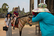 A young Asian boy sits on a horse and poses for his mother taking a photo with his sister standing by his side in the background is Angkor Wat Siem Reap, Cambodia. Angkor Wat is a temple complex in Cambodia and the largest religious monument in the world, with the site measuring 162.6 hectares. It is Cambodia's main tourist destination.