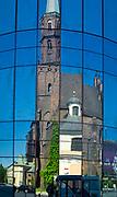 Odbicie kościóła św. Wojciech w szybach nowoczesnego budynku.