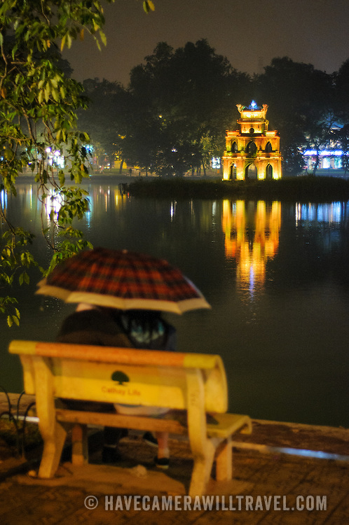 A couple sits under an umbrella on a park bench on the shores of Hoan Kiem Lake at night, with Turtle Tower (Thap Rua) in the background.