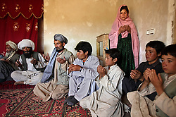Ghulam, 11, says a prayer with male family members to cement her engagement to Faiz, 40, Afghanistan, Sept. 11, 2005. She said she is sad to be getting engaged as she wanted to be a teacher. Her favorite class was Dari, the local language, before she was made to drop out of school. Married girls are seldom found in school, limiting their economic and social opportunities. Parents sometimes remove their daughters from school to protect them from the possibility of sexual activity outside of wedlock. It is hard to say exactly how many young marriages take place, but according to the Afghan women's ministry and women's NGOs, approximately 57 percent of Afghan girls get married before the legal age of 16. In addition, once the girl's father has agreed to the engagement, she is pulled out of school immediately. Early pregnancies also result in an increase in complications during child birth.