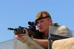 A British soldier, of the Duke of Wellingtons Regiment, serving with the Muliti National Division in beret and desert camouflage stands guard with an SA80 assault rifle and SUSAT, from the top of an army land rover, a position known as top cover, at Basra Air Station during Op Telic Iraq 2005