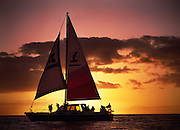 A sailboat coasts through calm waters at sundown in the Pacific Ocean off of Hawaii