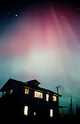 Alaska. Aurora Borealis light up the night sky with house in foreground.