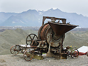 """A rusty old machine with gears and funnel rests by gravel-covered Kennicott Glacier in the Wrangell Mountains at Kennecott Mines National Historic Landmark within Wrangell-St. Elias National Park and Preserve, Alaska, USA. Old mine buildings, artifacts, and colorful history attract summer visitors. From McCarthy, a privately-operated shuttle takes visitors 5 miles to Kennecott. Remote McCarthy is connected to Chitina via the McCarthy Road spur of the Edgerton Highway. At the east end of McCarthy Road, visitors must park their vehicle and walk across the footbridge to McCarthy. After copper was discovered between the Kennicott Glacier and McCarthy Creek in 1900, the Kennecott town, mines, and Kennecott Mining Company were created and named after the adjacent glacier. Kennicott Glacier and River had previously been named after Robert Kennicott, a naturalist who explored in Alaska in the mid-1800s. The corporation and town stuck with a mistaken spelling of """"Kennecott"""" with an e (instead of """"Kennicott"""" with an i). Partly because alcoholic beverages and prostitution were forbidden in the company town of Kennecott, the neighboring town of McCarthy grew quickly to provide a bar, brothel, gymnasium, hospital, and school. The Copper River and Northwestern Railway reached McCarthy in 1911 to haul over 200 million dollars worth of ore 196 miles to the port of Cordova on Prince William Sound. By 1938, the worlds richest concentration of copper ore was mostly gone, the town was mostly abandoned, and railroad service ended. Not until the 1970s did the area began to draw young people for adventure and the big money of the Trans Alaska Pipeline project. Declaration of Wrangell-St. Elias National Park in 1980 drew adventurous tourists who helped revive McCarthy with demand for needed services. Wrangell-St. Elias National Park and Preserve (the largest National Park in the USA) is honored by UNESCO as part of an International Biosphere Reserve and UNESCO World Heritage Site."""