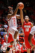 Utah guard Chris Hines (0) attempts to score against New Mexico guard Kendall Williams (10) and another defender during the first half of an NCAA college basketball game, Wednesday, Jan. 19, 2011, in Salt Lake City, Utah. (AP Photo/Colin E Braley)
