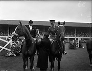 "03/08/1960<br /> 08/03/1960<br /> 03 August 1960<br /> R.D.S Horse Show Dublin (Wednesday). Mr. Kevin Boland T.D. Minister for Defence presenting the Hunting Horn Award (presented by the Irish Department of Defence) to Mrs Dawn Wofford on ""Hollandia"" and Captain W.A. Ringrose on ""Loch an Easpaig"", joint first prize-winners of the Epreuve de Puissance International Jumping Competition at the Dublin Horse Show."