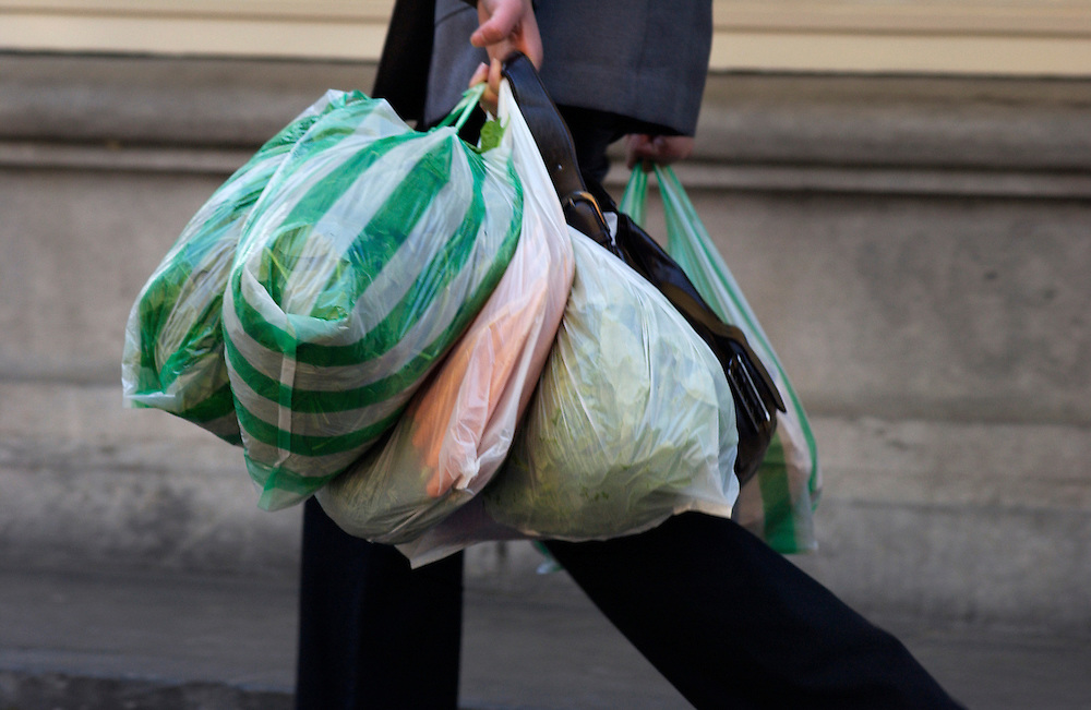 Nederland, Delft, 6 nov 2004<br />Plastic boodschappen tasjes in de hand van mensen die net van de markt komen. Elke stal zijn eigen zakje. Mensen gaan niet meer met een boodschappentas op pad.<br />Verspilling, economie, inkopen, <br />Foto (c) Michiel Wijnbergh/Hollandse Hoogte
