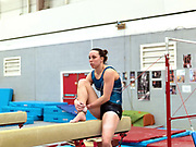 Portrait of gymnast, Beth Tweddle sitting on the balance beam during training at the City of Liverpool Gymnastics club, UK prior to the 2012 London Olympic Games. A three-time Olympian, Beth Tweddle competed in the 2004 Athens, 2008 Beijing, and 2012 London Olympic Games, where she took home a bronze medal on the uneven bars, the first Olympic medal for a British female gymnast. Tweddle retired in August 2013.