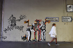 © Licensed to London News Pictures. 18/09/2017. London, UK. Members of the public view one of two new artworks outside the Barbican by street artist Banksy.  The artworks reference the late artist Jean-Michel Basquiat, whose own works will feature in his upcoming first ever UK exhibition at the Barbican Gallery. (The work on the left has been applied by a rival street artist) Photo credit : Stephen Chung/LNP