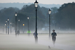 © Licensed to London News Pictures. 22/09/2021. London, UK. Members of the public exercise during a misty morning on Blackheath Common in South East London. Temperatures are expected to rise with highs of 22 degrees forecasted for parts of London and South East England today . Photo credit: George Cracknell Wright/LNP