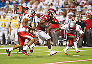 Sep 10, 2011; Little Rock, AR, USA; Arkansas Razorback running back Ronnie Wingo Jr. (20) carries the ball as New Mexico Lobos defensive backs Daunte Caro (31) and Anthony Hooks (6) attempt the tackle during the second half of a game at War Memorial Stadium.  Mandatory Credit: Beth Hall-US PRESSWIRE