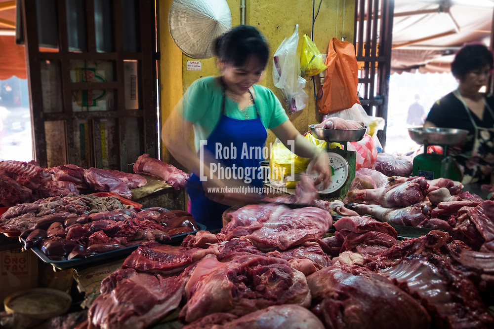 A female butcher preparing meat for a customer in Hoi An Central Market