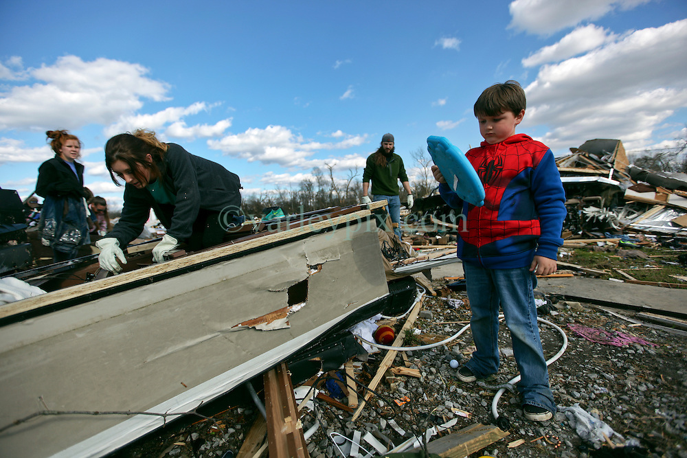 24 February 2016. Sugar Hill RV Park, Convent, Louisiana.<br /> Scenes of devastation following a deadly EF3 tornado touchdown. 2 confirmed dead. <br /> Rylan Johnson (7 yrs) helps recover family belongings from the flipped trailers and cars dotting the landscape.<br /> Photo©; Charlie Varley/varleypix.com