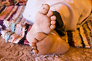 The dried and cracking feet of Berber nomad camel guide El-Hussein Sbiti resting on a rug at camp in the dunes of Erg Zehar, outside M'Hamid, Morocco. Sbiti, like many berber nomads in the region, has found opportunity in the new tourism trade burgeoning since the settling of tensions between Morocco and neighboring Algeria.