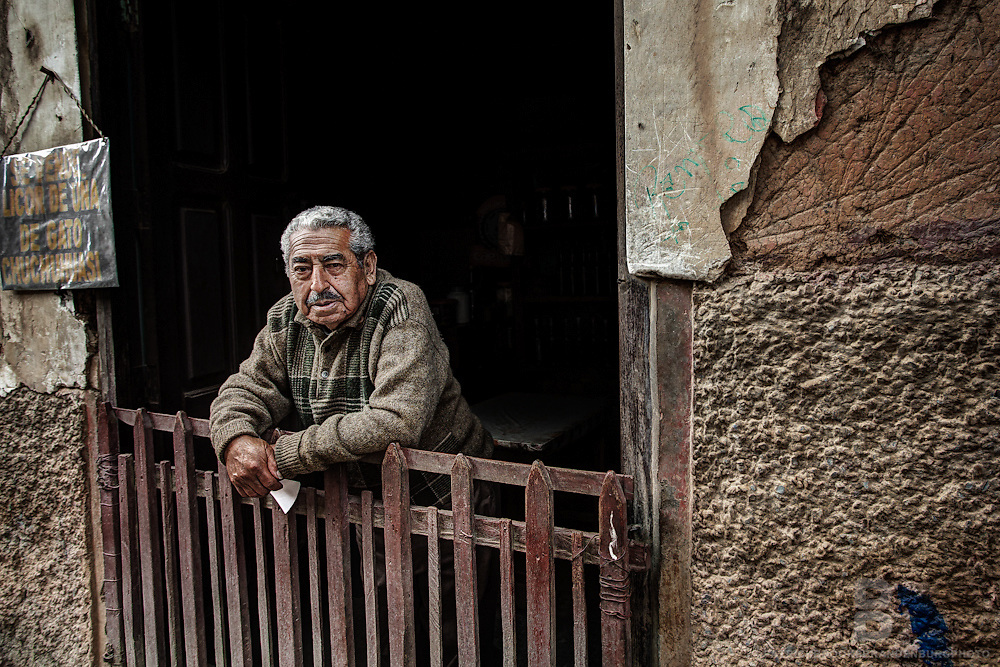 A small shop owner looks out of his shop and poses for a portrait in Coroico, Bolivia.