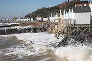 Beach huts being eroded by winter storm waves, Felixstowe, Suffolk, England
