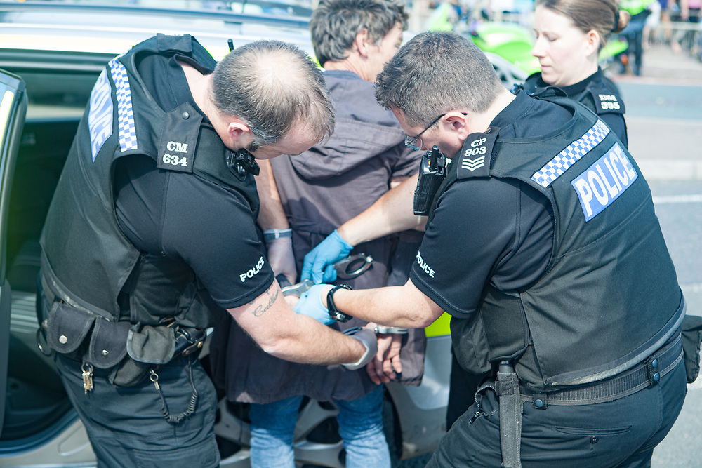 a man is put in handcuffs by Police as he is arrested at Brighton Pier