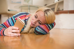 Beautiful young woman using smart phone and lying on floor in the living room, Bavaria, Germany