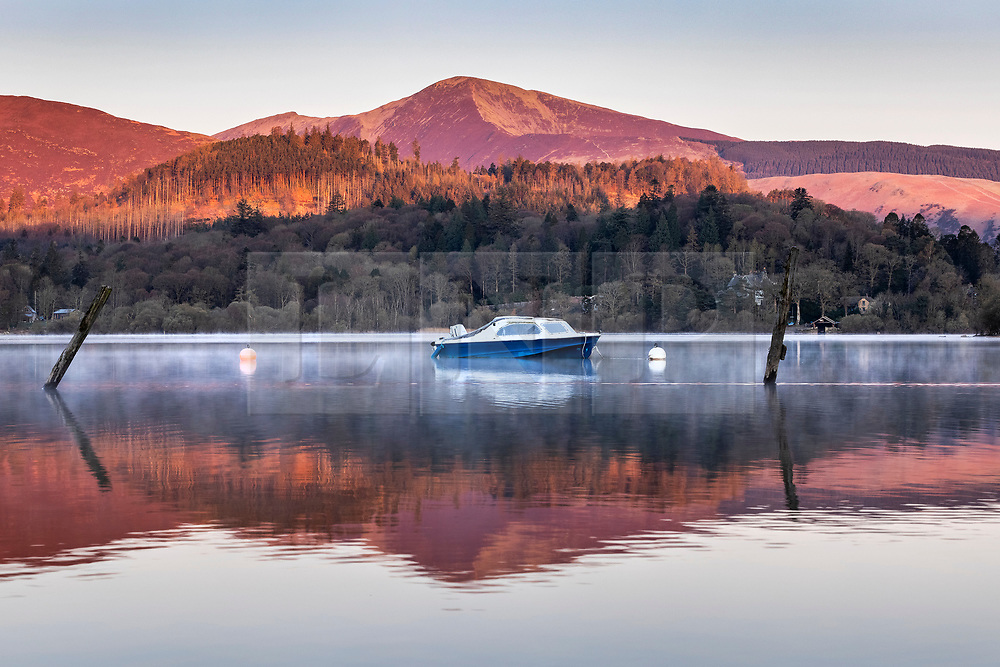 © Licensed to London News Pictures. 12/04/2021. Keswick UK. The mountains that surround Derwentwater in Keswick glow pink & red as the sun rises this morning in Cumbria. Photo credit: Andrew McCaren/LNP