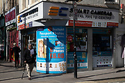 Street scene in Whitechapel in East London, England, United Kingdom. A digital camera shop advertisment for passport photos.