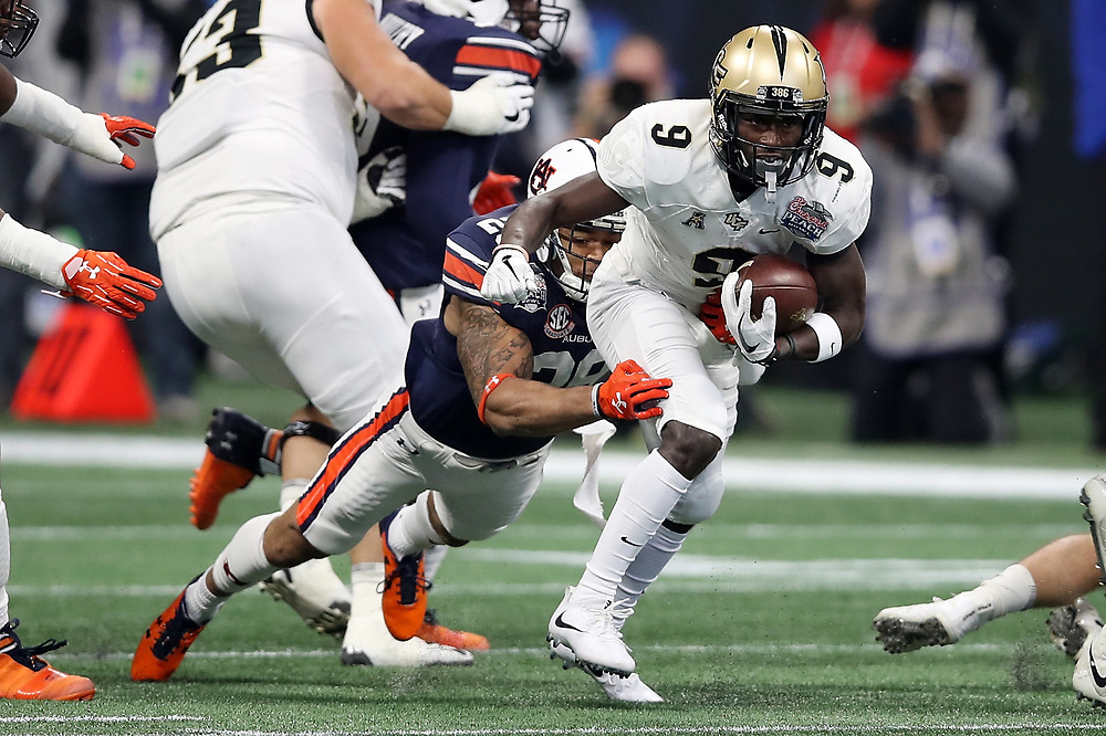 UCF Knights running back Adrian Killins Jr. (9) is tackled by Auburn Tigers defensive back Tray Matthews (28) on a run during the 2018 Chick-fil-A Peach Bowl NCAA football game on Monday, January 1, 2018 in Atlanta. (Jason Parkhurst / Abell Images for the Chick-fil-A Peach Bowl)