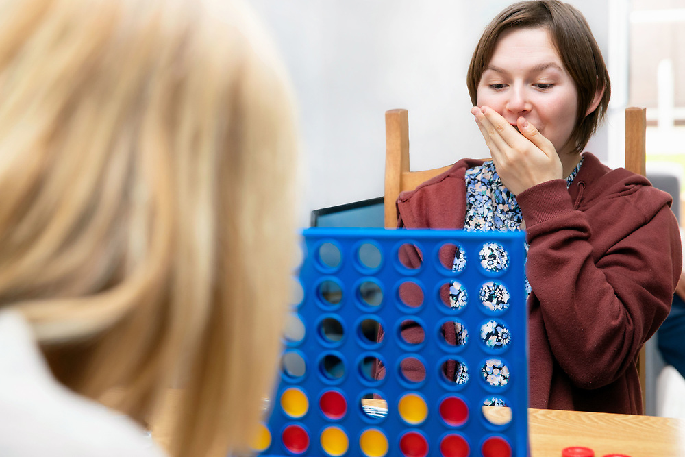 Support worker with service user playing a game.<br /> Client  - Allerton, an integrated social care, housing, and development company.
